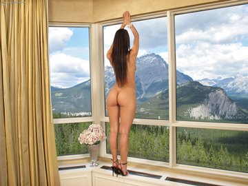 (b) standing in front of window, looking at Cascade Mountain
